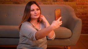 Plus formatmodell med l?ngt h?r som g?r n?tta selfie-foto genom att anv?nda smartphonen i hemtrevlig hem- atmosf?r arkivfilmer