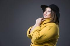 Plus formatmodemodell i gult lag och svart hatt fet kvinna på grå bakgrund, överviktig kvinnlig kropp Arkivbilder