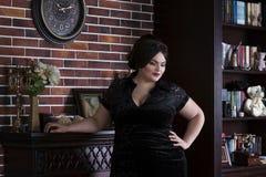 Plus formatmodemodell i svart aftonklänning fet kvinna på lyxig inre, överviktig kvinnlig kropp arkivbild