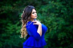Plus groottemannequin in blauwe kleding in openlucht, schoonheidsvrouw met professionele make-up en kapsel stock afbeelding