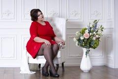 Plus groottemannequin in rode avondjurk, vette vrouw op luxe binnenlands, te zwaar vrouwelijk lichaam, volledig lengteportret stock afbeelding