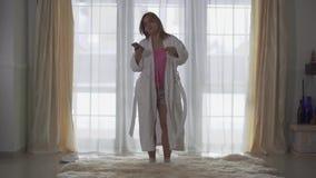 Plus groottemeisje in witte lange badjas die voor groot vloer-aan-plafond venster dansen die aan muziek in hoofdtelefoons luister stock video