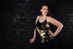 Plus groottemodel in een gouden blouse en zwarte jeans op een achtergrond van de baksteenzolder royalty-vrije stock foto
