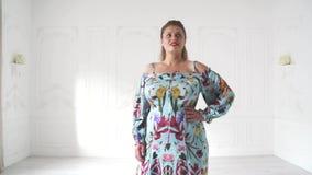 Plus groottemodel in het mooie kleding stellen in heldere studio Het mollige vrouw stellen in mooie uitrusting stock video