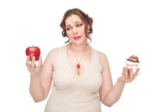 Plus groottevrouw die keus tussen appel en gebakje maken stock foto