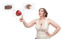 Plus groottevrouw die keus tussen gezond en ongezond voedsel maken stock foto