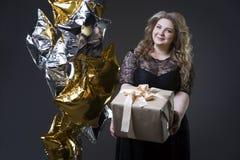 Plus groottevrouw in zwarte dres met giftdoos en ballons op grijze achtergrond Royalty-vrije Stock Foto's