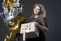 Plus groottevrouw in zwarte dres met giftdoos en ballons op grijze achtergrond Stock Foto