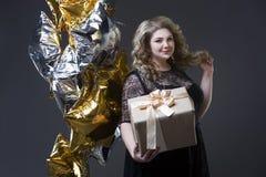 Plus groottevrouw in zwarte dres met giftdoos en ballons op grijze achtergrond Stock Fotografie