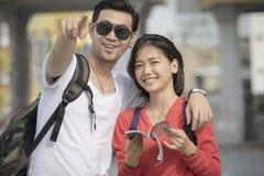 Plus jeune destination de déplacement heureuse asiatique d'homme et de femme de sac à dos Photos libres de droits