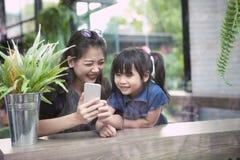 Plus jeune femme asiatique et enfants regardant au salon futé d'écran de téléphone à la maison image libre de droits
