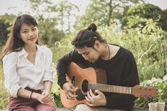 Plus jeune homme asiatique et femme jouant la guitare avec émotion de bonheur images stock