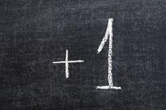Plus one. Symbols handwritten on the school blackboard Stock Photography