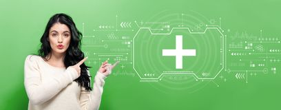 Plus sign with young woman. Pointing on a green background royalty free stock photos