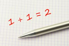 1 plus 1. Simple equation on a squared paper sheet. Math for children royalty free stock photo