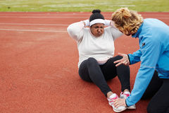Plus-size African woman doing sit-ups exercise guided by personal trainer Stock Photography