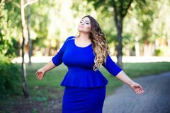 Plus size fashion model in blue dress outdoors, beauty woman with professional makeup and hairstyle, freedom concept. Plus size fashion model in blue dress Royalty Free Stock Image