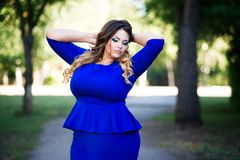 Plus size fashion model in blue dress outdoors, beauty woman with professional makeup and hairstyle, freedom concept. Plus size fashion model in blue dress Royalty Free Stock Photo