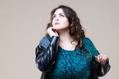 Plus size fashion model in casual clothes, fat woman on beige background, overweight female body. Plus size fashion model in casual clothes, fat woman on beige Stock Images