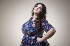 Plus size fashion model in casual clothes, fat woman on beige background, overweight female body Stock Photography