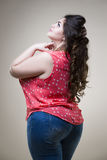 Plus size fashion model in casual clothes, fat woman on beige studio background, overweight body Royalty Free Stock Photo