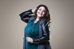 Plus size fashion model in casual clothes, fat woman on beige studio background Stock Photo
