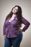 Plus size fashion model in casual clothes, fat woman on beige studio background, overweight female body Royalty Free Stock Images