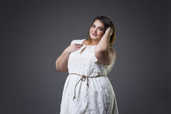 Plus size fashion model in casual clothes, fat woman on gray background, overweight female body Stock Image