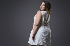 Plus size fashion model in casual clothes, fat woman on gray background, overweight female body Royalty Free Stock Image