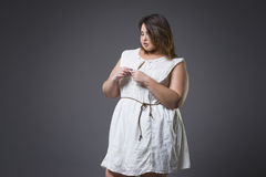 Plus size fashion model in casual clothes, fat woman on gray background, overweight female body. Plus size fashion model in casual clothes, fat woman on gray Stock Photo