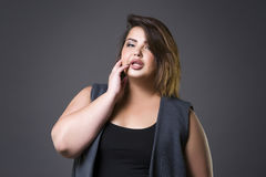 Plus size fashion model in casual clothes, fat woman on gray background, overweight female body Royalty Free Stock Photography