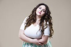Plus size fashion model, fat woman on beige background. Plus size fashion model in casual clothes, fat woman on beige studio background royalty free stock photography