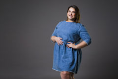 Plus size fashion model in casual jeans clothes, fat woman on gray background, overweight female body Stock Photography
