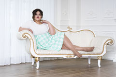 Plus size fashion model, fat woman on luxury interior, overweight female body. Professional make-up and hairstyle stock photo