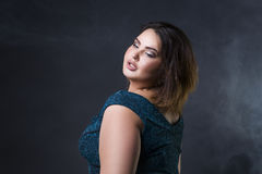 Plus size fashion model in green evening dress, fat woman on black background, portrait with professional makeup Stock Photos
