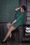 Plus size fashion model in green evening dress, fat woman on luxury interior, overweight female body Royalty Free Stock Photography