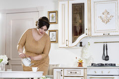 Plus size fashion model on kitchen, fat woman on luxury interior, overweight female body. Professional make-up and hairstyle Royalty Free Stock Photos