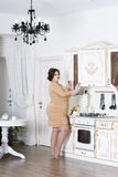 Plus size fashion model on kitchen, fat woman on luxury interior, overweight female body Royalty Free Stock Images