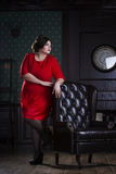 Plus size fashion model in red evening dress, fat woman on luxury interior. Full length portrait, professional make-up and hairstyle royalty free stock image