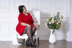Plus size fashion model in red evening dress, fat woman on luxury interior, overweight female body, full length portrait. Professional make-up and hairstyle stock image