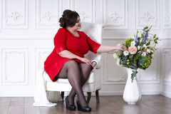 Plus size fashion model in red evening dress, fat woman on luxury interior. Professional make-up and hairstyle stock images