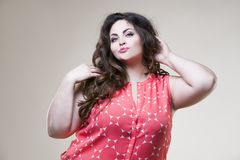 Plus size fashion model, fat woman on beige background. Plus size fashion model in casual clothes, fat woman on beige studio background stock photo