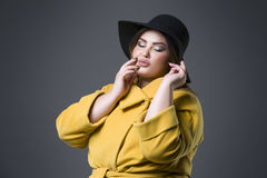 Plus size fashion model in yellow coat and black hat, fat woman on gray background, overweight female body Royalty Free Stock Images