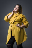 Plus size fashion model in yellow coat and black hat, fat woman on gray background, overweight female body. Plus size fashion model in yellow coat and black hat Stock Photography