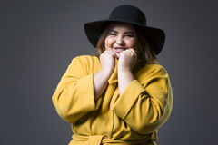 Plus size fashion model in yellow coat and black hat, fat woman on gray background, overweight female body. Plus size fashion model in yellow coat and black hat Stock Photo