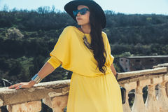 Plus size fashion model. Young stylish woman wearing yellow maxi dress, black hat, sunglasses and handbag walking in the city street. Spring fashion outfit Royalty Free Stock Photos
