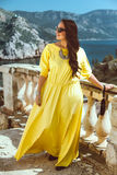 Plus size fashion model. Young stylish woman wearing yellow maxi dress, sunglasses and clutch walking in the city street. Spring fashion outfit, elegant look Stock Photo