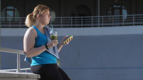 Overweight woman jogger drinking green smoothie
