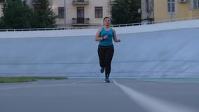 Overweight woman runner training on stadium track. Plus size female jogger in sportswear running forwards along city stadium track during intense cardio training stock footage