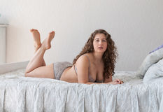 Plus size female in lingerie lying on the bed legs crossed Stock Image